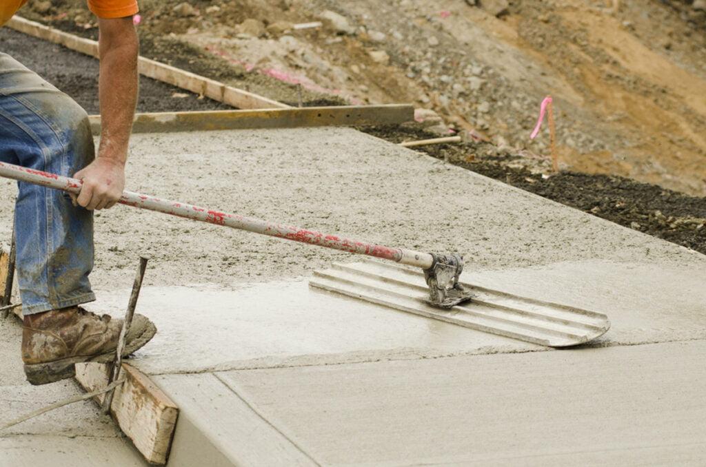 A mason using hand trowel to install a new sidewalk in Seattle, WA